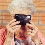 Activiteitenbegeleider oude vrouw met camera